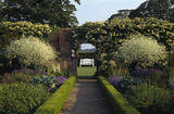 View through an arch in the garden at Felbrigg looking towards a white wooden bench
