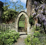 An unusual pointed archway in the garden at Croft Castle, with a glimpse of an orchard beyond