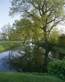 View of the moat at Sissinghurst with trees reflected in the water