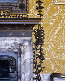 Detail of the corner of the bolection-moulded chimney surround and part of the part-grained, part-gilded softwood carving in the Dining Room at Hanbury Hall