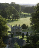 Atmospheric view across the parkland of Lanhydrock showing the seventeenth century gatehouse built by John, Lord Robartes, the tall sentinel yews and the arboretum beyond