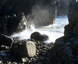 A view of Kynance Cove between the rocks, the water spills over pebbles and the spray is caught by the morning sunlight