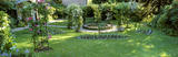 A panoramic view of Alexa's Rose Garden at Peckover with climbing roses trained over metal arches and a circular pond at the centre of the garden