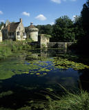 Scotney Castle with the Ashburnham Tower across the moat, where many lily pads are floating on the water