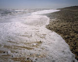 Surf on Minsmere Beach at Dunwich Heath showing a rocky beach with the sea breaking on it