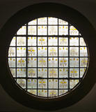 Back-lit view of the Bull's Eye window at Red House showing the William Morris motto 'Si Je Puis' (If I Can)