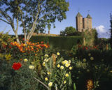Looking across a display of various kinds of Dahlias in the Cottage Garden towards the Towers of the Castle standing out against the blue sky