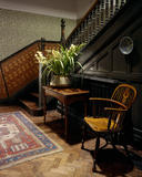 View of the Visitors Staircase at Wightwick Manor including hall table with arranged flowers, chair and Japanese rush matting dado