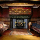 The blue tiled inglenook fireplace with stone manetlpiece in the Great Parlour at Wightwick Manor