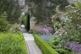 Narrow paved path bordered by neat hedging in the Rose Garden in June at Sissinghurst Castle Garden, near Cranbrook, Kent