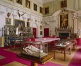View of the Saloon at Calke Abbey showing the glazed oak display case, billiard display case, table with alligator skull and portrait of Lady Frances Harpur and her son Henry by Tilly Kettle