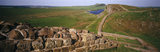 Panoramic view of a milecastle and the continuation of the wall, with Highshield Crags and Crag Lough in the distance