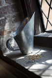 Grain and scoop on a windowsill at the C18th working Winchester City Mill, Hampshire, where corn is ground into flour