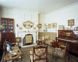 View of the Drawing Room at Sunnycroft, showing the glass- fronted display cabinet, white marble fireplace, sofa and pianola