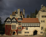 The half timbered South Front of Cragside against a stormy sky