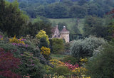 Scotney Castle viewed from the 'Bastion' spring with colourful shrubs visible in the foreground
