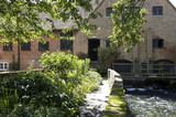 Exterior of the C18th Winchester City Mill, Hampshire, with the water which had powered the wheel rushing through the sluices