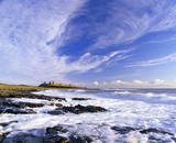 Long view along the shore at Craster towards Dunstanburgh Castle, Northumberland