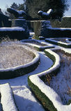 The snow covered paths in the Fuchsia Garden leading between two topiary birds to the Pool Garden beyond