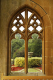 A view of the terrace garden planting through the tracery of one of the stone windows of the porch at Tyntesfield, Wraxall, North Somerset