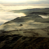 A view from Mam Tor of Winnats Pass filled with morning mist