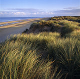 A view across the Marram and Sea-lyme sand dunes at Formby Point towards the shore line where the sea laps gently on the yellow sandy beach