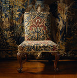 Close-up of George I walnut chair covered with gros-point needlework against a 17th century Brussels tapestry depicting a terraced garden, in the Great Hall at Packwood House