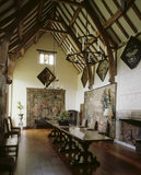 The Great Hall at Packwood House showing the timber ceiling, oak refectory table, 17th century Brussels tapestry depicting a terraced garden and bay window with heraldic glass