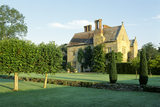 View of the house at Bateman's from across the lawn in late afternoon light