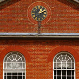 Close view of the Stable Block at Mottisfont Abbey, with fine gauged red brick, the clock and arched windows