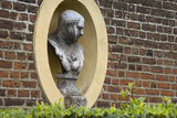 A bust of a Roman Emperor in a niche in the wall of the North Forecourt at Ham House, Surrey