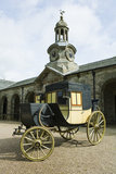 The early 1800s Travelling Chariot, with the stable block beyond