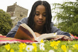 Visitor reading in the garden at Buckland Abbey, Devon.