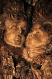 Close view of part of the C17th wood carving by Grinling Gibbons in the Carved Room at Petworth House showing the heads of two cherubs