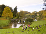 The Palladian Bridge at Stourhead, Wiltshire, with a family visiting the landscape garden to enjoy the autumn colours