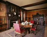 View of the Small Dining Room at Oxburgh Hall showing the table, chairs, fireplace and large wooden buffet