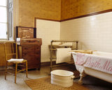 Bathroom with a tiled section around a basin and free standing iron bath with clawed feet at Dunham Massey, showing a heated towel rail & a luxurious crocodile-skin travelling toilet case