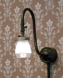A gaslight (lit) in the 1880s Living Room of the Birmingham Back to Backs with wallpaper behind of a floral design on a pink background