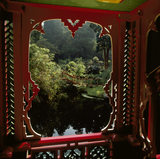 A view looking out from the Chinese Temple, showing the detail of the ornate wooden window, and looking out towards the pool in the area known as China
