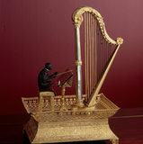 A musical box from the Sultana Room, in the form of a gilded harp and a monkey, holding a baton, conducting