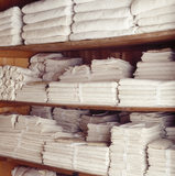 The linen cupboard open to show bundles of C18th and mainly C19th napery