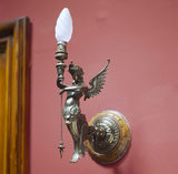 Detail of an electric light fitting featuring a winged figure with a fish tail holding a torch, in the Turret Landing at Sunnycroft