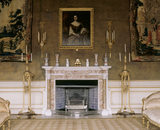 Partial view of the marble chimneypiece including the giltwood torcheres on tripod stands in the Saloon at Chirk Castle