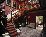 The Staircase Hall at Sunnycroft, showing the parquet flooring, rugs and collection of Lander family portraits, furnished in baronial style