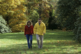 View of a couple in red and yellow fleeces walking through Sheffield Park on an autumn's day