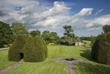 A view of the two yew houses on the large lawn at the fifteenth-century Great Chalfield Manor, Wiltshire
