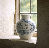 The Old Kitchen at Woolsthorpe Manor showing a close-up view of a large tobacco jar on the window ledge inscribed in blue letters 'TABACQ VIRGINY'