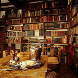 The walls of the Study lined with books, on the desk is a large tobacco jar,a bone crocodile,a wooden box decorated in gesso with oak & ash leaves,inscribed with a quotation from puck of pook's hill