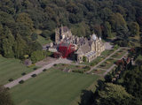 Aerial view of Tyntesfield from the West, showing West & South fronts of the house, the formal terrace garden & the Chapel at rear of the house close to the woodland