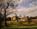 Looking across the lawn, sunlight bathes the west front of Dudmaston